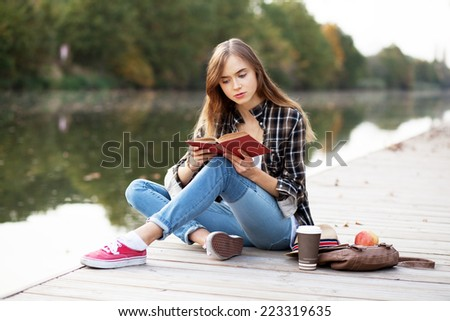 Young beautiful girl sitting on a pier - stock photo