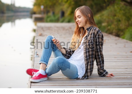 Young beautiful girl sitting on a pier, listening to music from her smartphone - stock photo