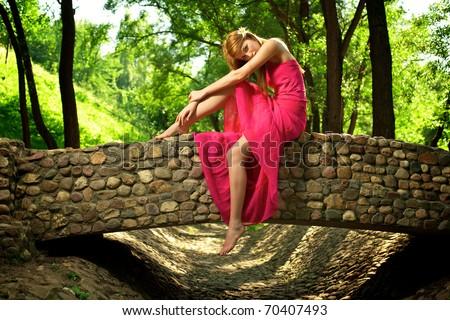 Young beautiful girl sitting on a stone bridge - stock photo