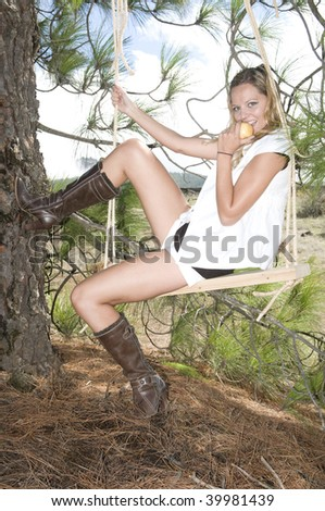 Young beautiful girl sitting on a swing - stock photo