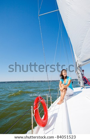 Young beautiful girl sitting on a yacht - stock photo