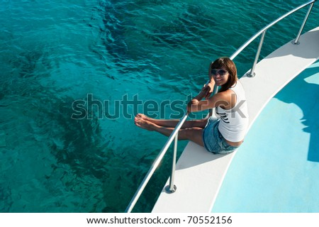 Young beautiful girl sitting on a yacht with his legs hanging in the blue sea - stock photo