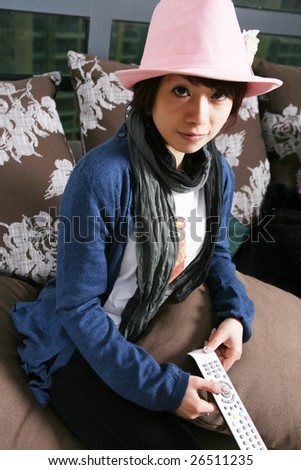 young beautiful girl sitting on chair watch TV