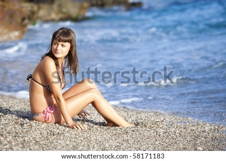 Young beautiful girl sitting on the beach.