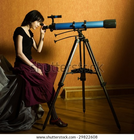 Young beautiful girl sitting on the bed looking to the telescope - stock photo