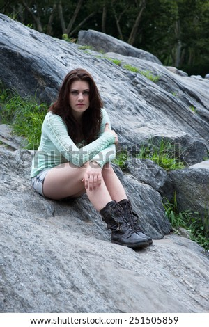 Young beautiful girl sitting on the boulders in the park - stock photo