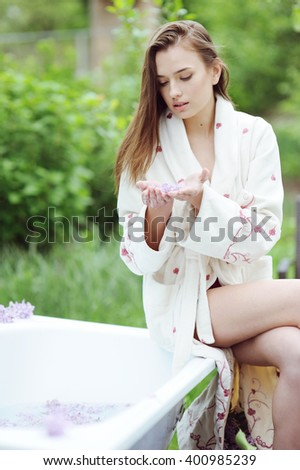 Young beautiful girl sitting on the edge of a bath in the garden