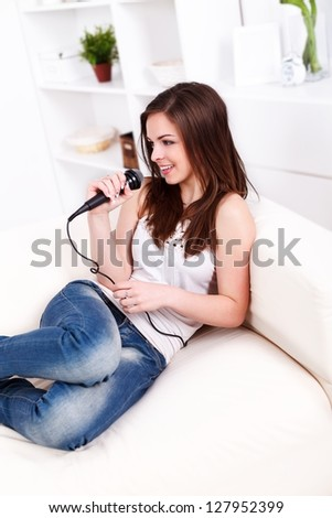 Young beautiful girl sitting on the sofa and singing into the microphone