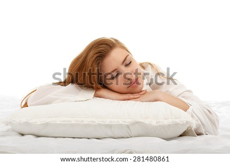 Young beautiful girl sleeps in the bed hugging a pillow on his stomach isolated on white background. - stock photo
