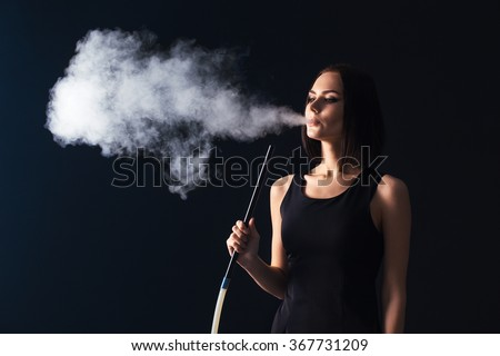 Young, beautiful girl smokes a hookah. It produces smoke from his mouth. Business style clothing. The pleasure of smoking. - stock photo