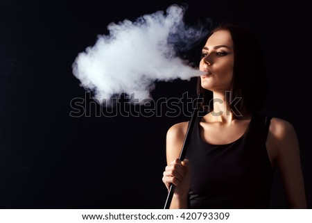 Young, beautiful girl smokes a hookah. It produces smoke from his mouth. Business style clothing. The pleasure of smoking.