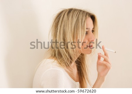 young beautiful girl smoking cigarette - stock photo