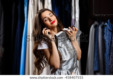 Young beautiful girl speaking on phone in shopping mall.