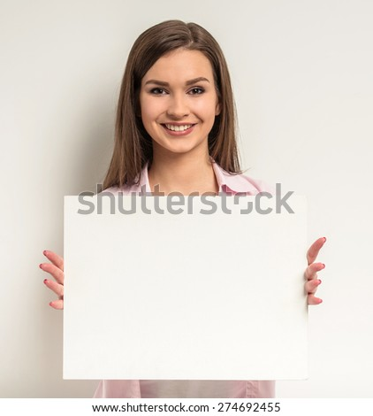Young beautiful girl standing on grey background and holding empty paper billboard with copy space for text.
