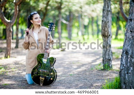 Young beautiful girl standing on her knees with a black guitar in a beige coat.