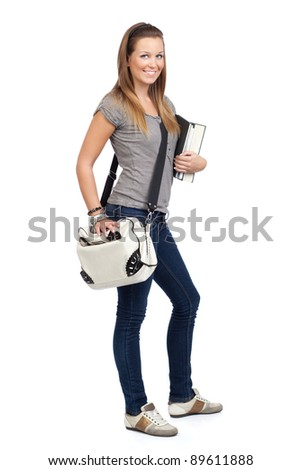 Young beautiful girl standing with books and bag, isolated on white
