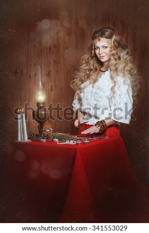 Young beautiful girl stands near a fortune teller desk with a lamp and candles. Card reading. Divination - stock photo