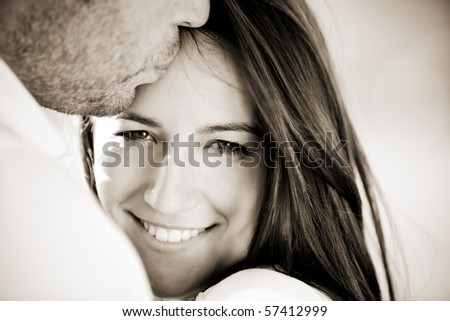 Young beautiful girl staring at camera while being kissed