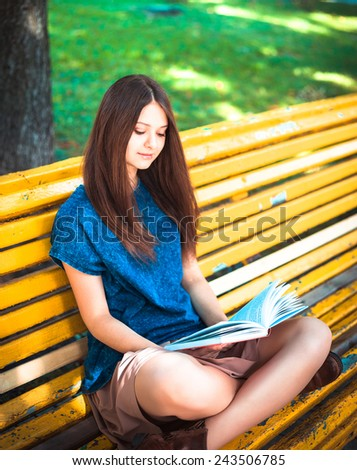 Young beautiful girl student sitting on yellow bench and reading book  - stock photo