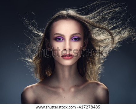 Young beautiful girl studio portrait with streaming hair. Wind waves hair.