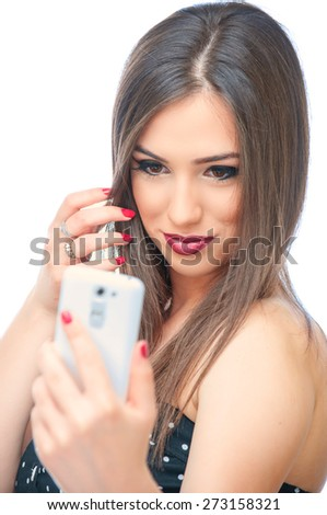 Young beautiful girl taking selfie with mobile phone, isolated on white background - stock photo