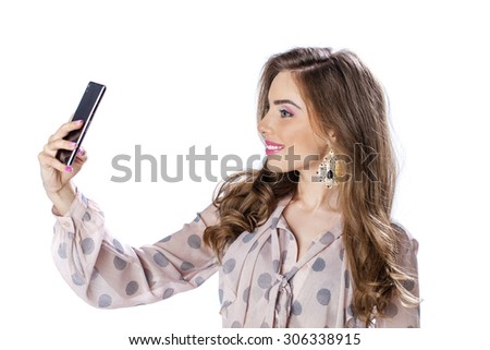 Young beautiful girl taking selfie with mobile phone, isolated on white background