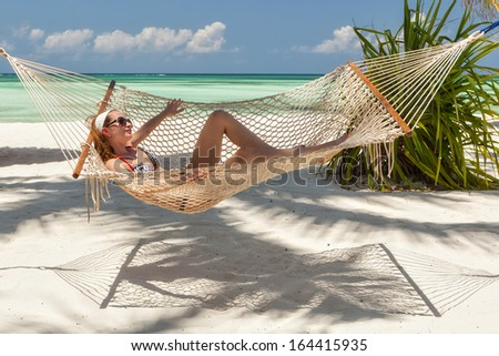 Young beautiful girl taking sunbath swinging in hammock, Pongwe Beach, Zanzibar, Tanzania