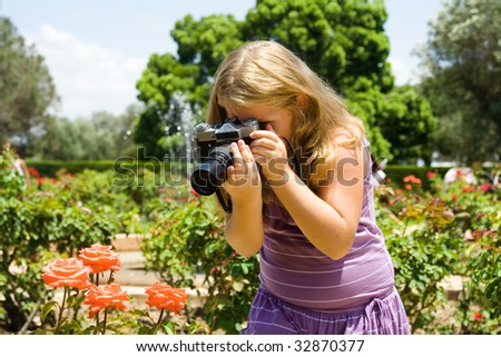Young  beautiful girl the blonde photographs roses with SLR camera - stock photo