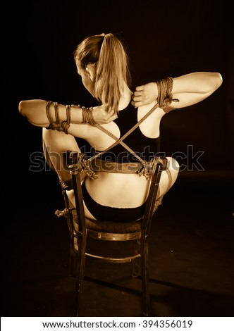 young beautiful girl tied to a chair - stock photo