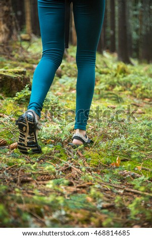Young beautiful girl tourist athletic figure walks in the woods. Female legs walking on forest trail