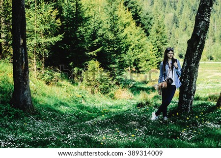 young beautiful girl traveler sitting in flower meadow in spring mountains with backpack