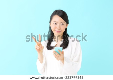 young beautiful girl using mobile phone, against blue background