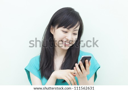 young beautiful girl using mobile phone, against pale green background