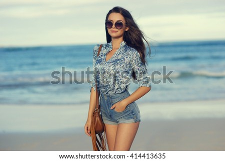 Young beautiful girl walking at the beach at sunset. Stylish woman with long hair standing in blouse and jeans shorts