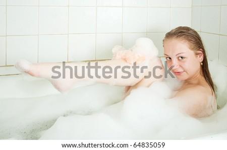 young beautiful girl washing in a bath - stock photo