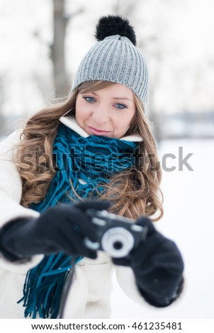 Young beautiful girl with a camera, snowy idyll, the woman photographed subject is in front of you