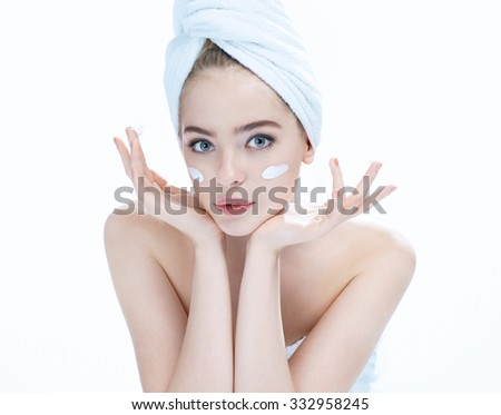 Young beautiful girl with a face cream / blue-eyed blonde girl applying the cream to the face - isolated on white background - stock photo