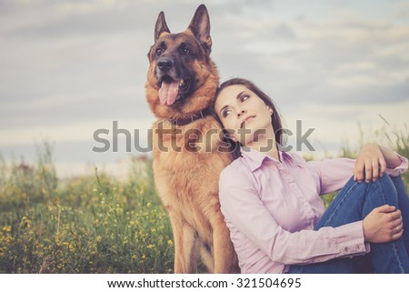 Young beautiful girl with a German shepherd playing on the lawn at the day time - stock photo