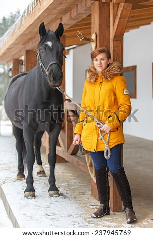 Young beautiful girl with a horse near the wooden stable  - stock photo