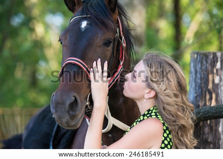 Young beautiful girl with a horse on nature - stock photo