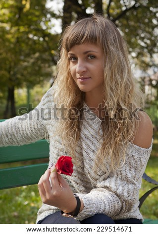 Young beautiful girl with a rose in hand on nature background - stock photo