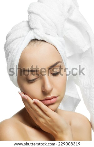 Young beautiful girl with a towel on his head after a shower touching her face. Perfect clean skin.  Isolated on a white background. - stock photo