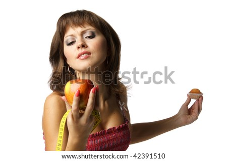 Young beautiful girl with apple and cake in her hands on a white background. Healthy food concept
