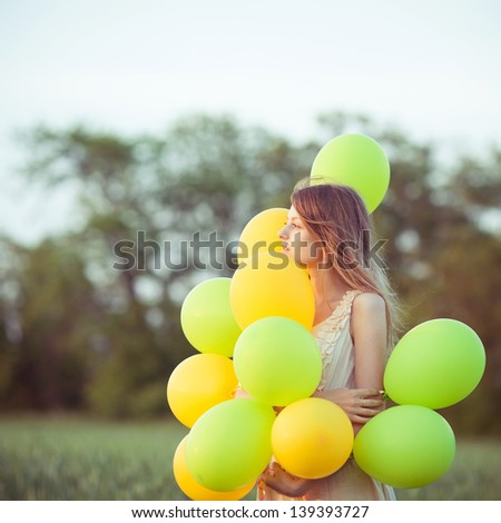 young beautiful girl with baloons in the field