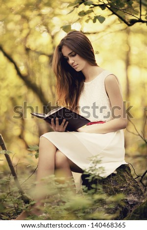 young beautiful girl with book in the forest - stock photo