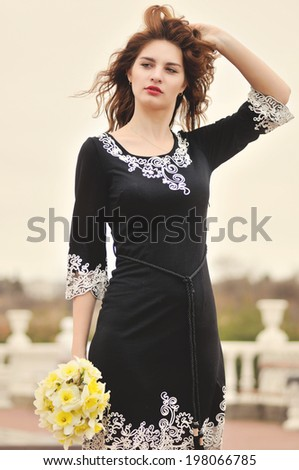young beautiful girl with daffodils - stock photo
