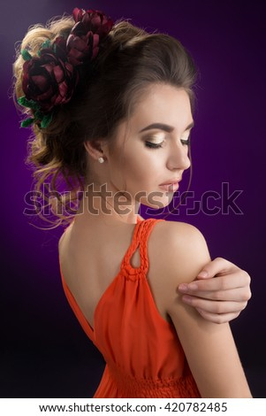 Young beautiful girl with flowers in her hair. Gorgeous spring and summer portrait. Provocative wedding make up. Tender lady in dress smiling and posing in studio on violet background. Not isolated.  - stock photo