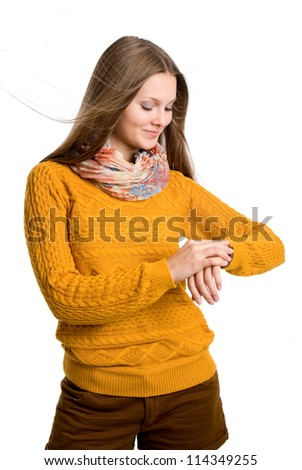 Young beautiful girl with flying hair looking at his watch.isolated over a white background - stock photo