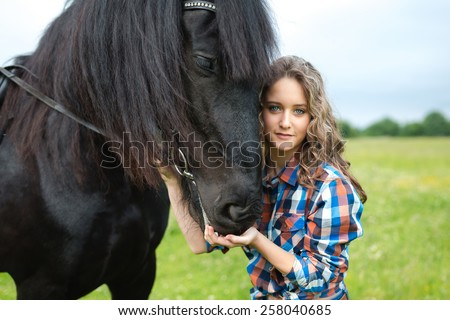 Young beautiful girl with frisian horse standing in the meadow at summer time - stock photo