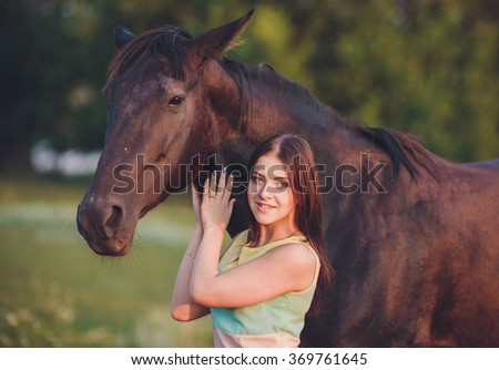 Young beautiful girl with frisian horse standing in the meadow at summer time